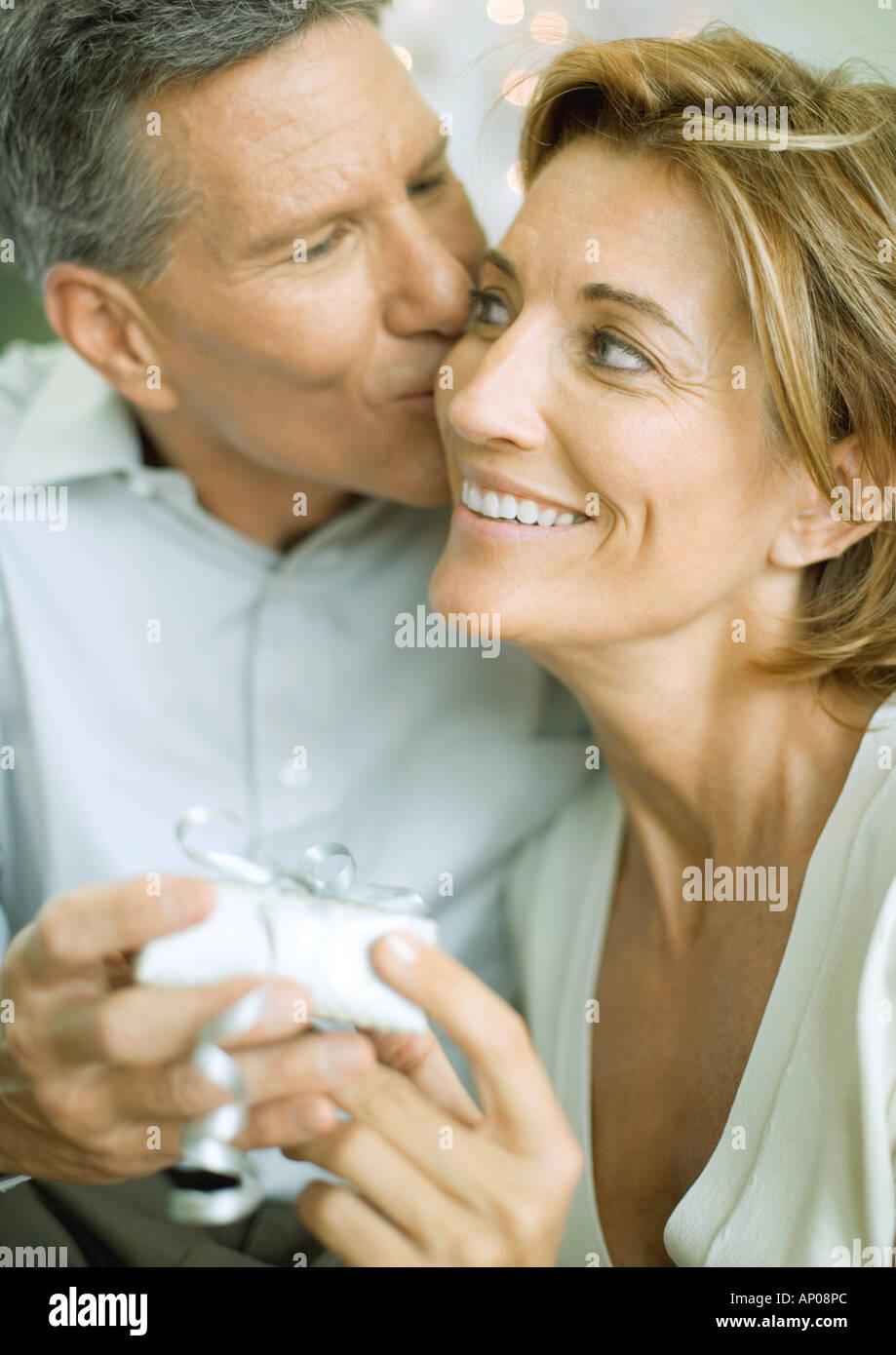 Austausch von Weihnachtsgeschenk paar, Mann küssen Frau auf Wange ...