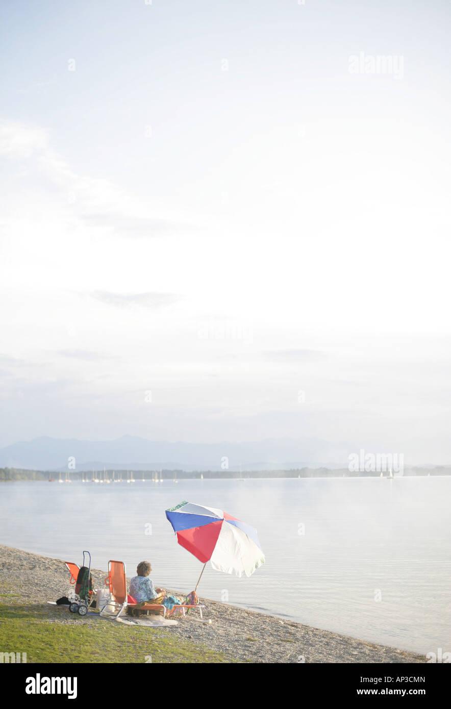 Frau mit Sonnenschirm auf See-Ufer, Ambach, Starnberger See, Bayern ...