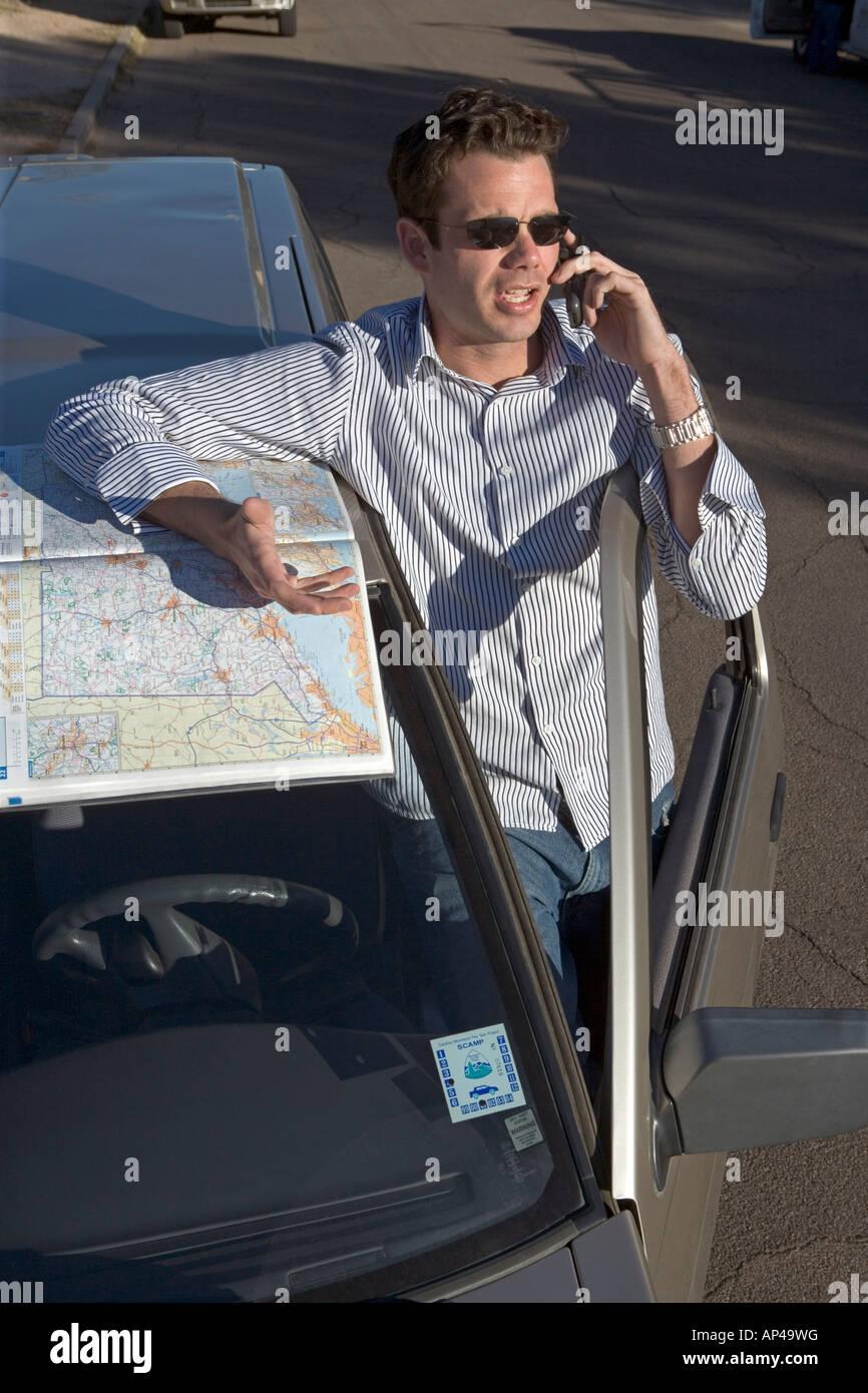 Ein Mann verloren, während fahren einen Fahrplan während auf einem Handy überprüft Stockbild