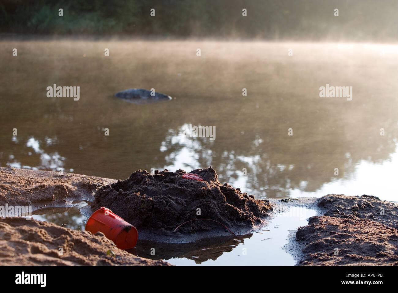 Verlassene Sandburg mit Spielzeug an einem nebligen See Stockbild