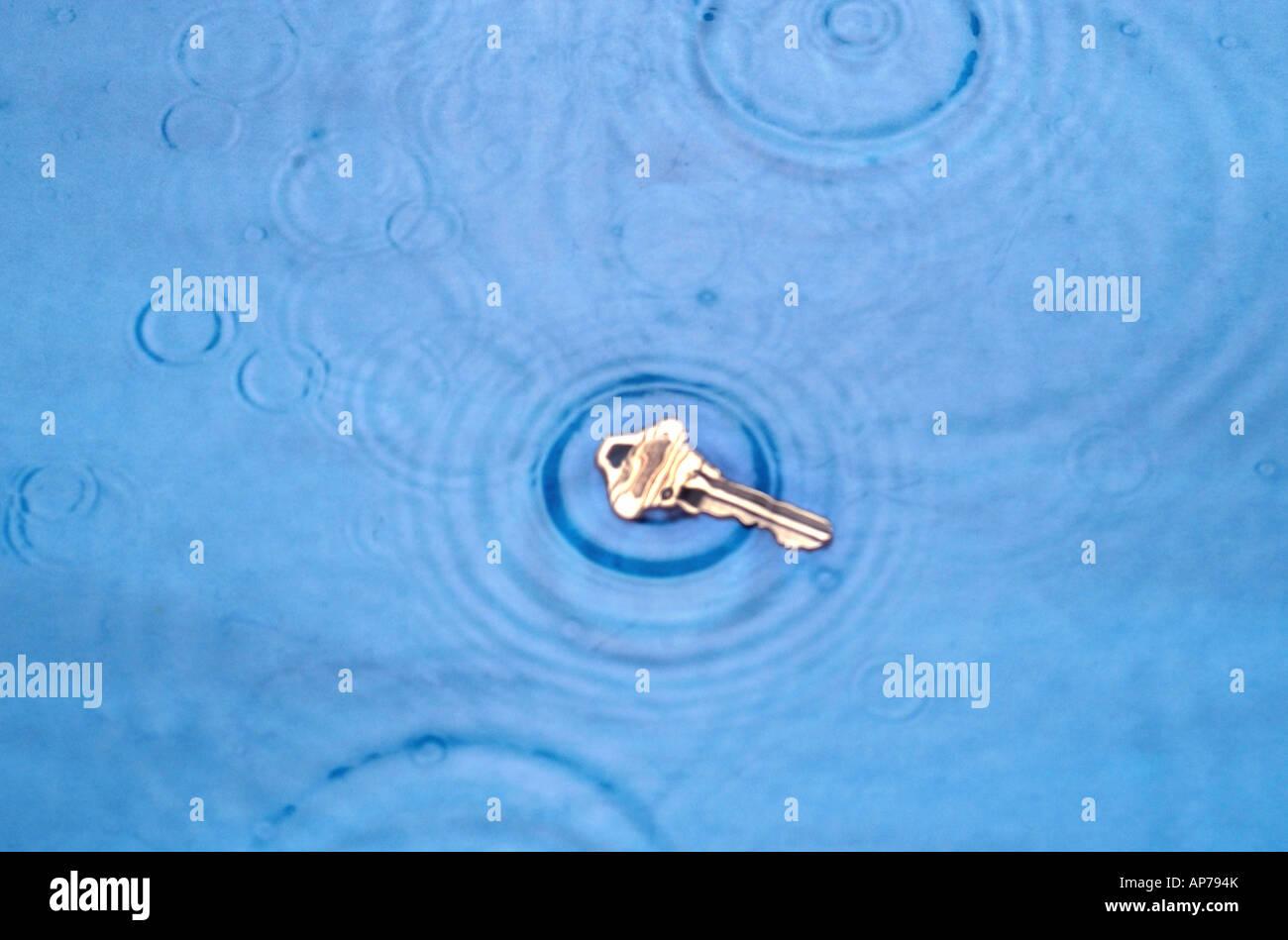 verlorener Schlüssel in Pfütze im Regen Tropfen nass Stockbild