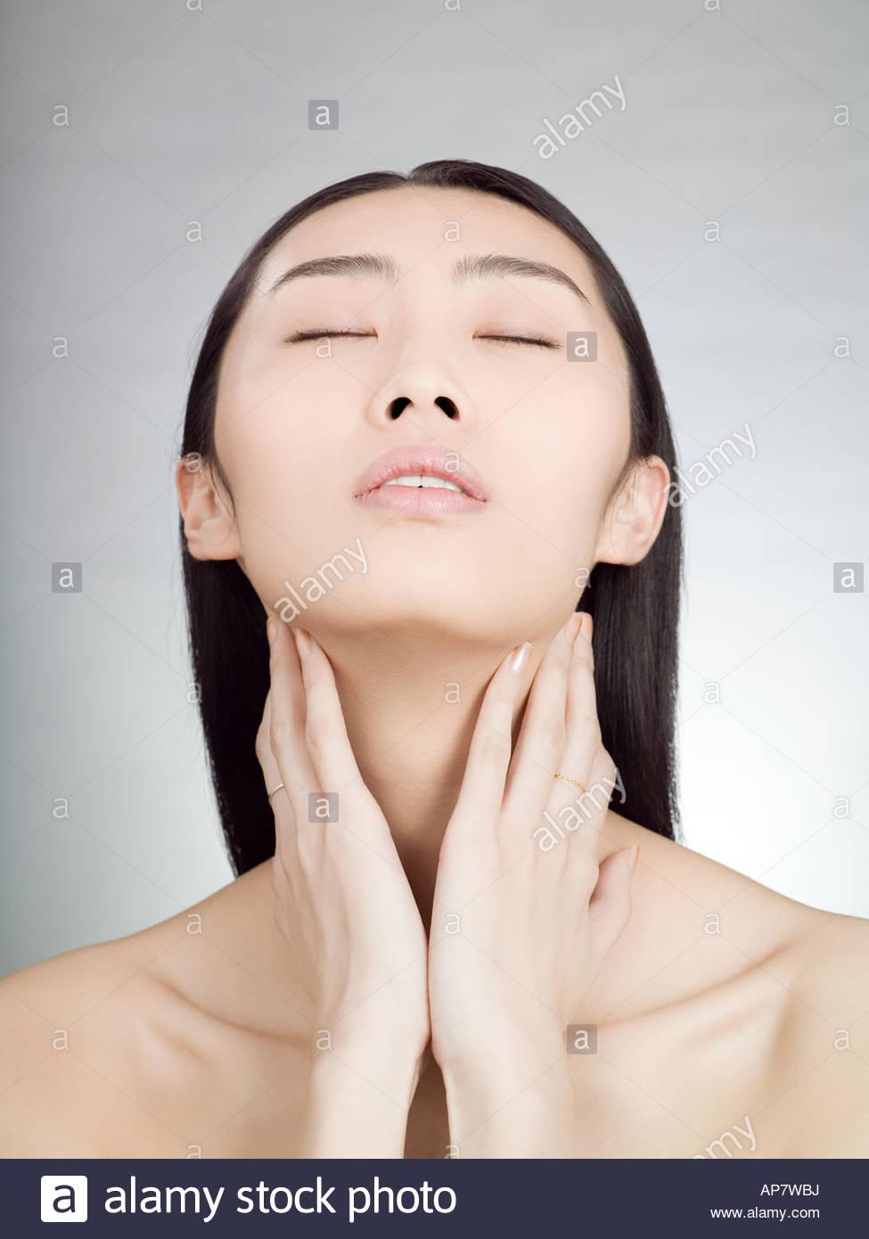 Chinesische Frau, die den Hals berühren Stockfoto