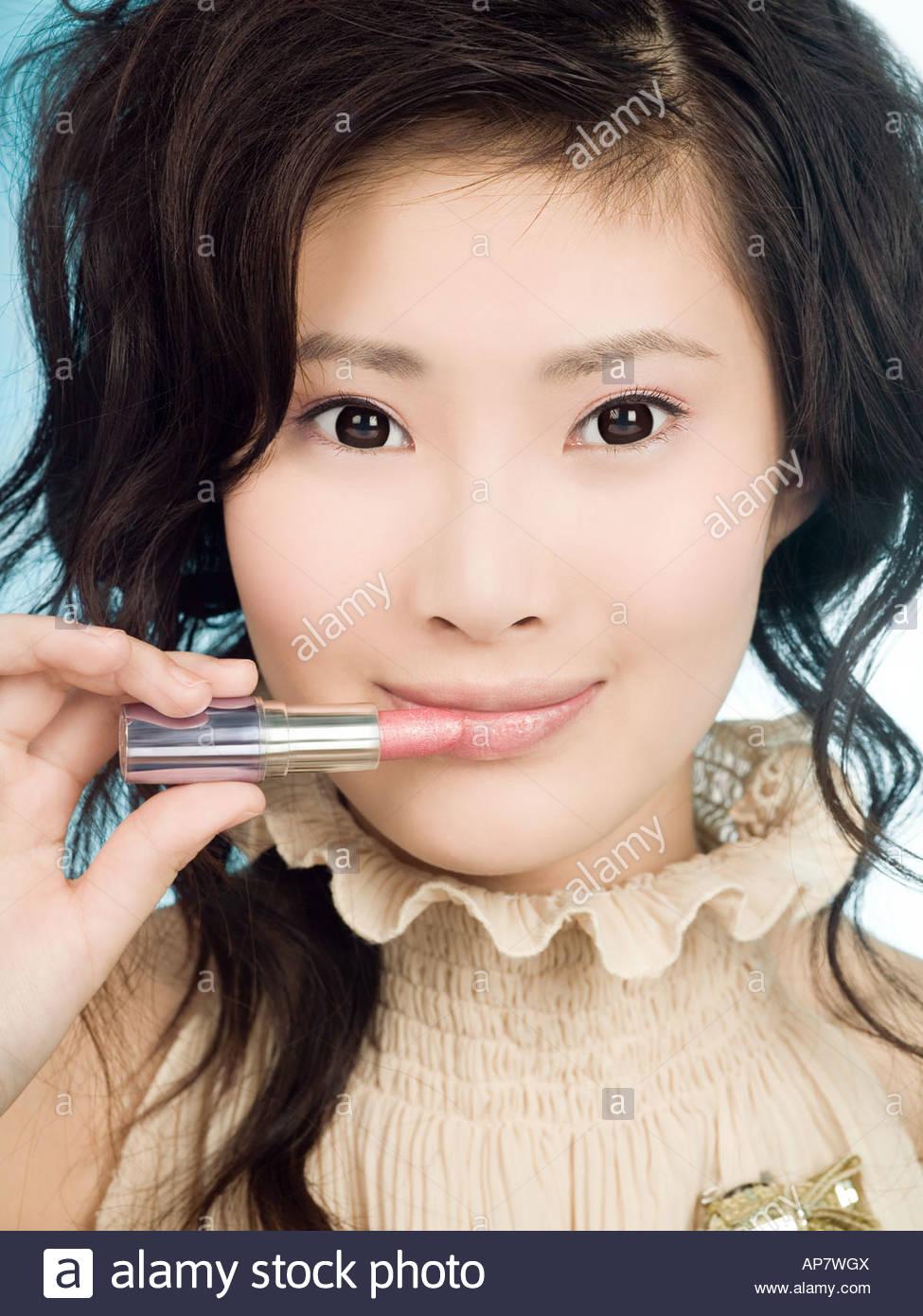 Chinesische Frau Auftragen von Lippenstift Stockbild