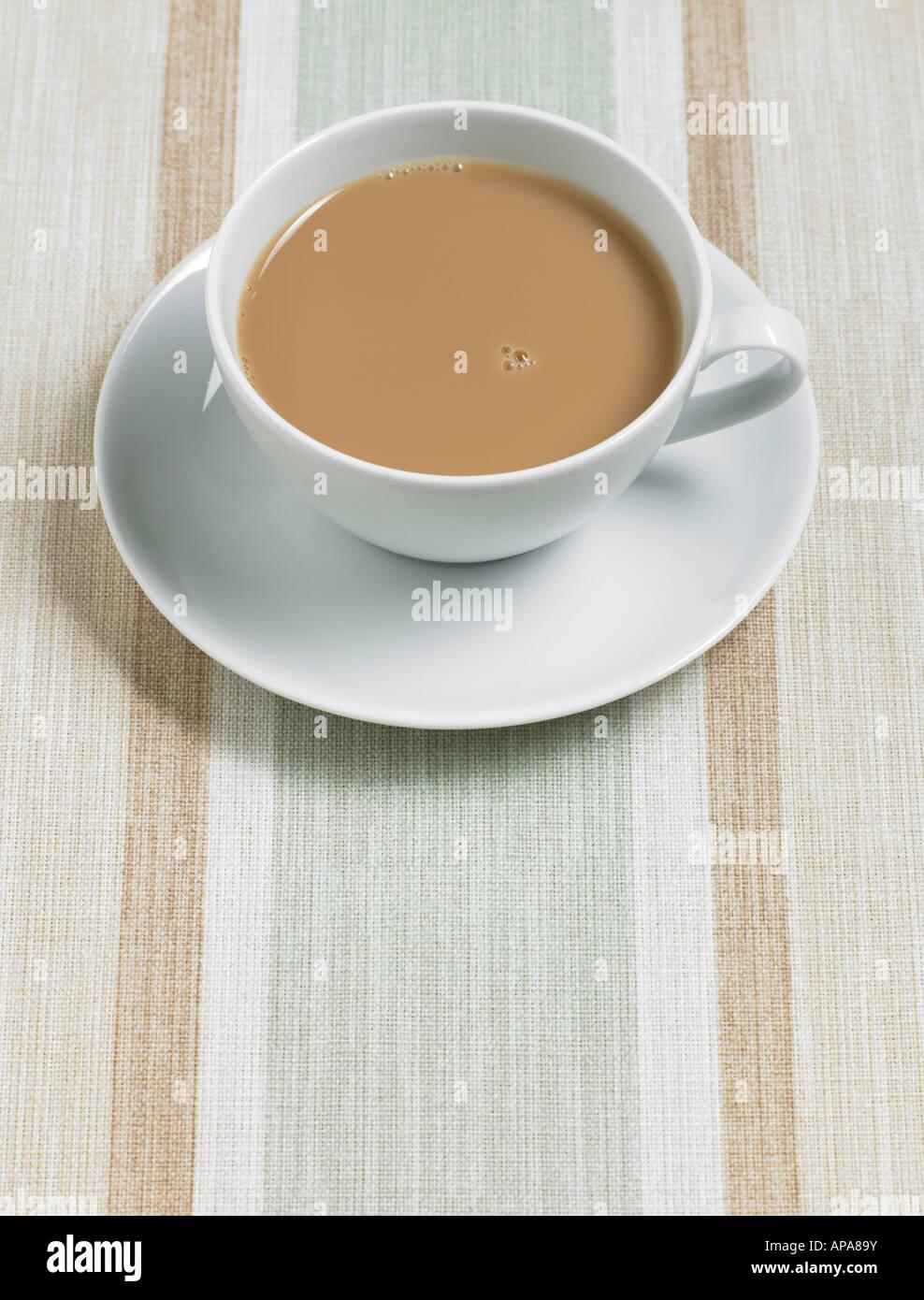 Teetasse und Untertasse auf Tischdecke Stockbild