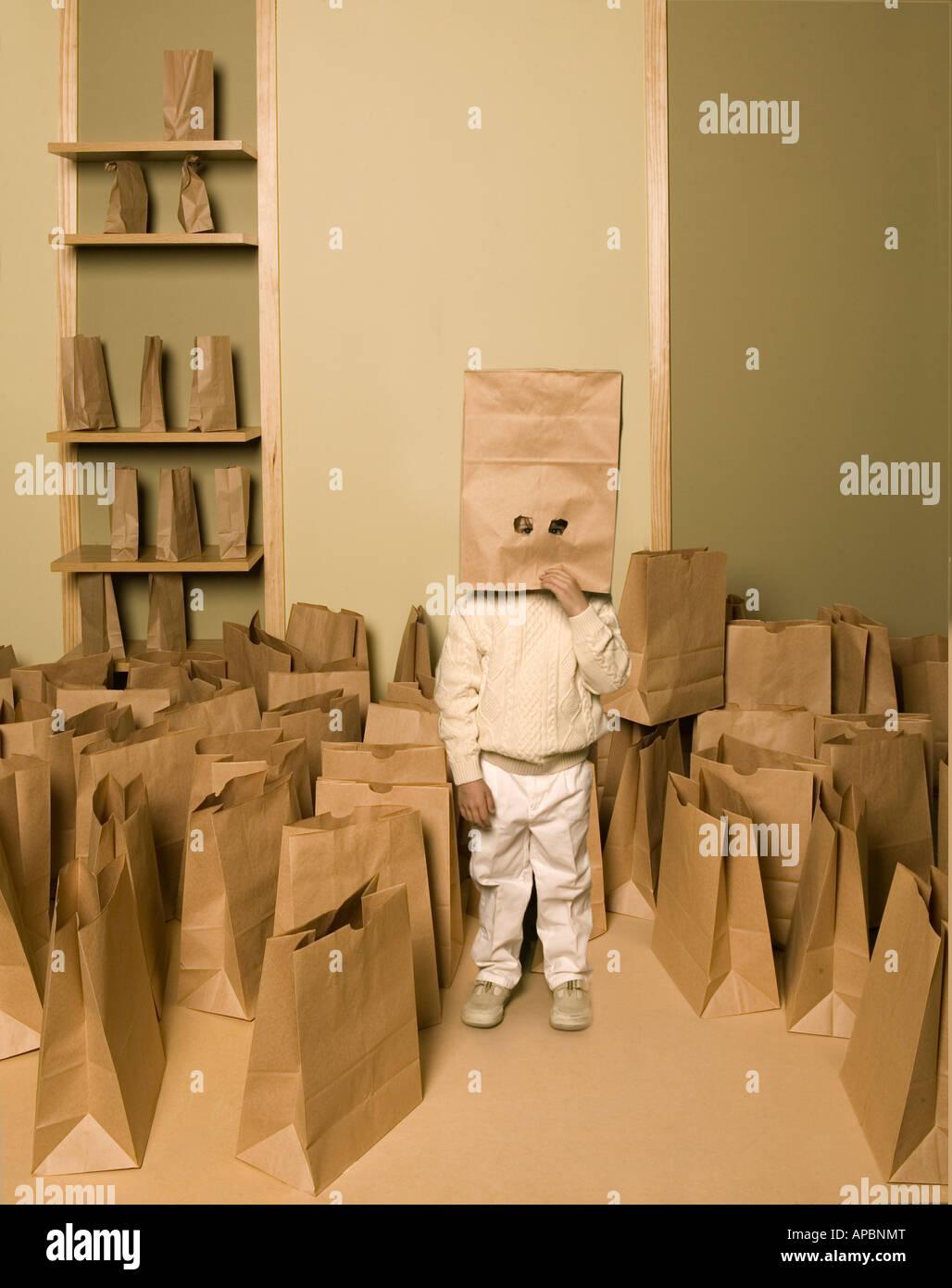 junges Kind steht unter mehreren Papiertüten mit Papiertüte auf dem Kopf mit ausgeschnittenen Augen als Stockbild