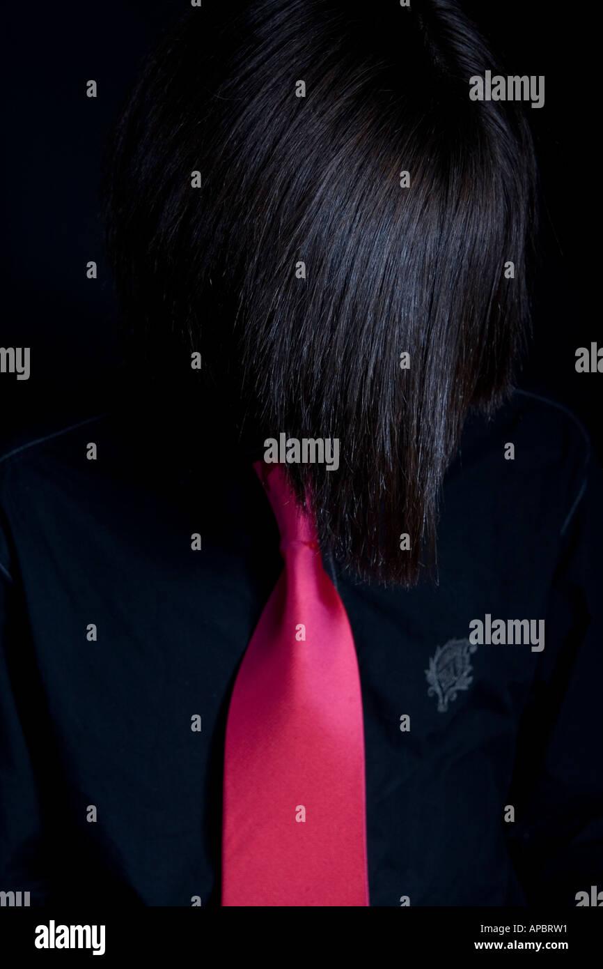 Mode-pop-Stil-Bild von einem jungen Mann mit glänzenden Haaren und langen Fransen in rosa Krawatte und schwarzen Hemd Stockbild