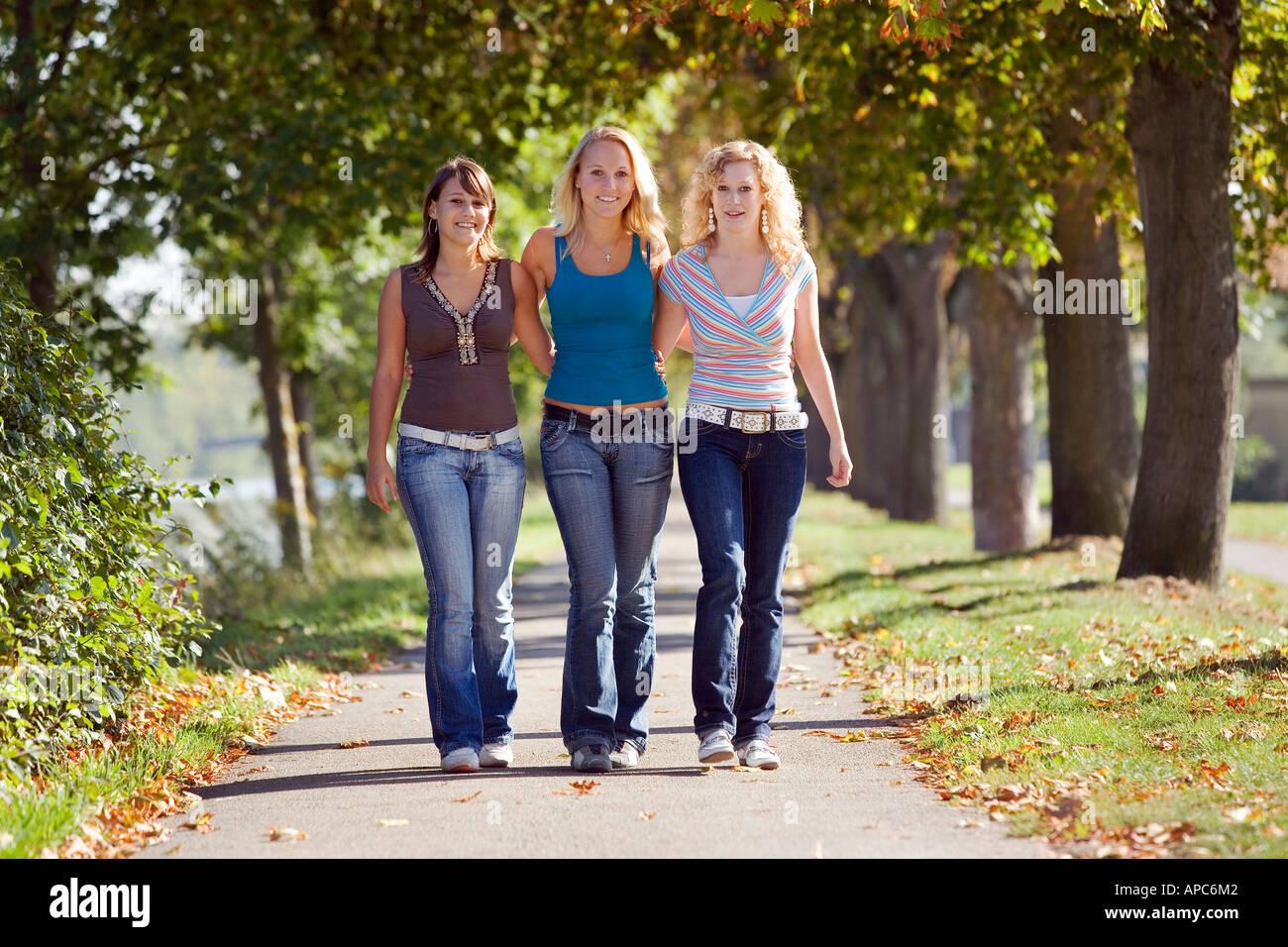 Drei junge Frauen, die zu Fuß durch einen park Stockbild