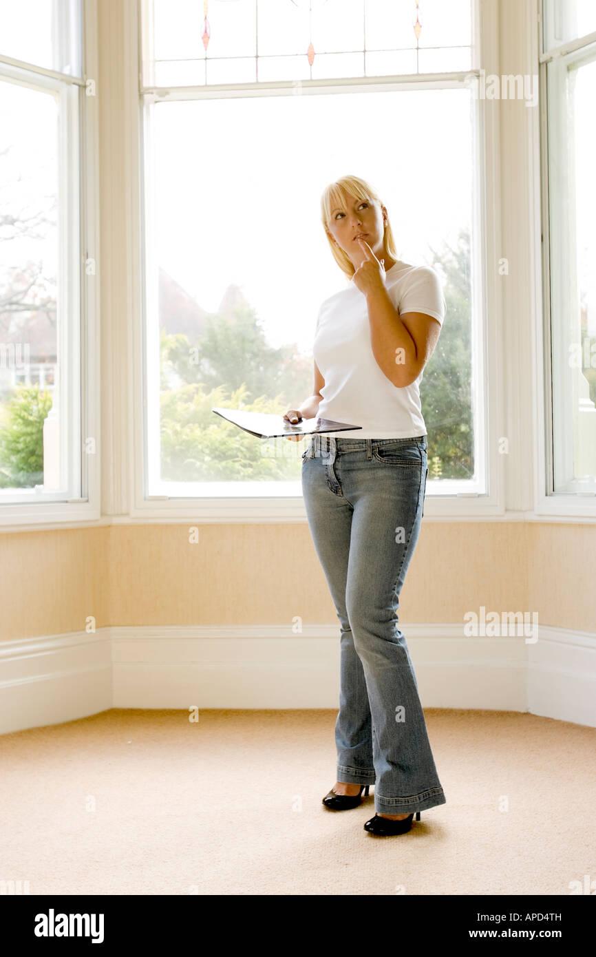 Frau auf der Suche um ein Emply Haus Stockbild