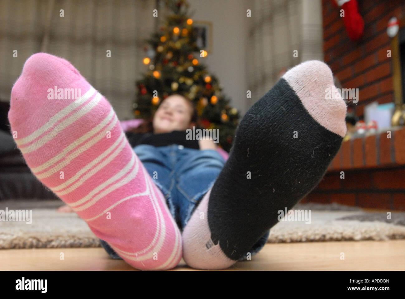 ein Mädchen mit ungeraden Socken liegen vor einem Weihnachtsbaum ...