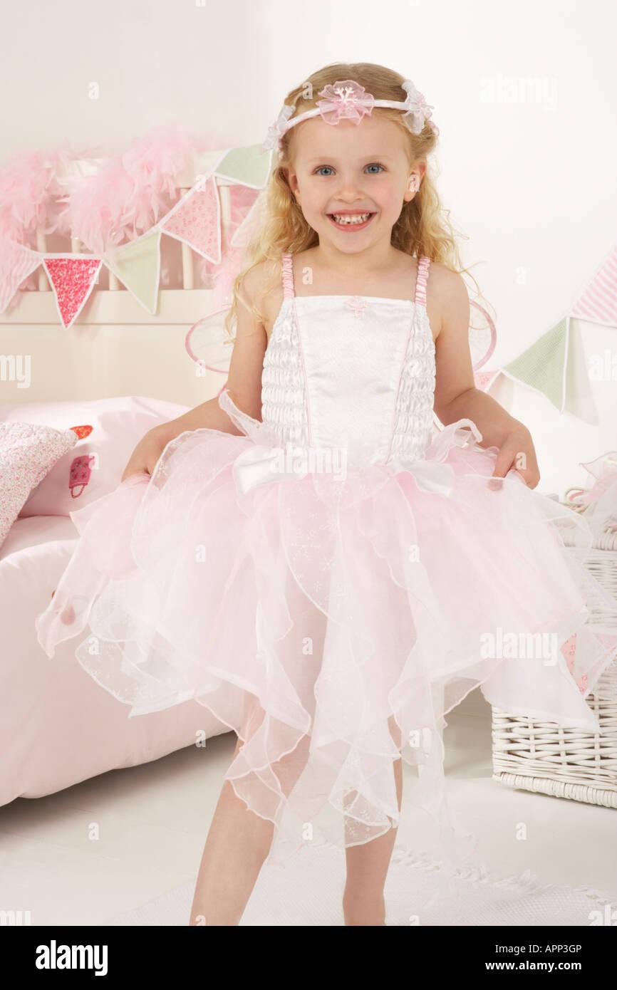 ein Mädchen spielt, putzt sich in ihrem Schlafzimmer und ist als eine weiße Fee verkleidet Stockbild