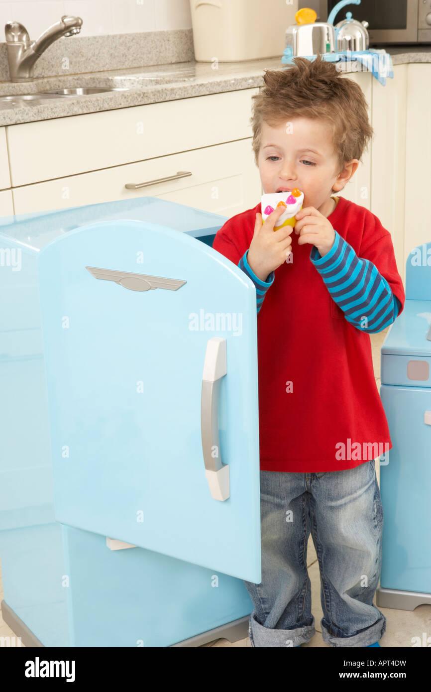 ein Junge spielt in einer Küche mit einem Kühlschrank Spielzeug, er steht in der Tür, während er vorgibt, einen Stockfoto