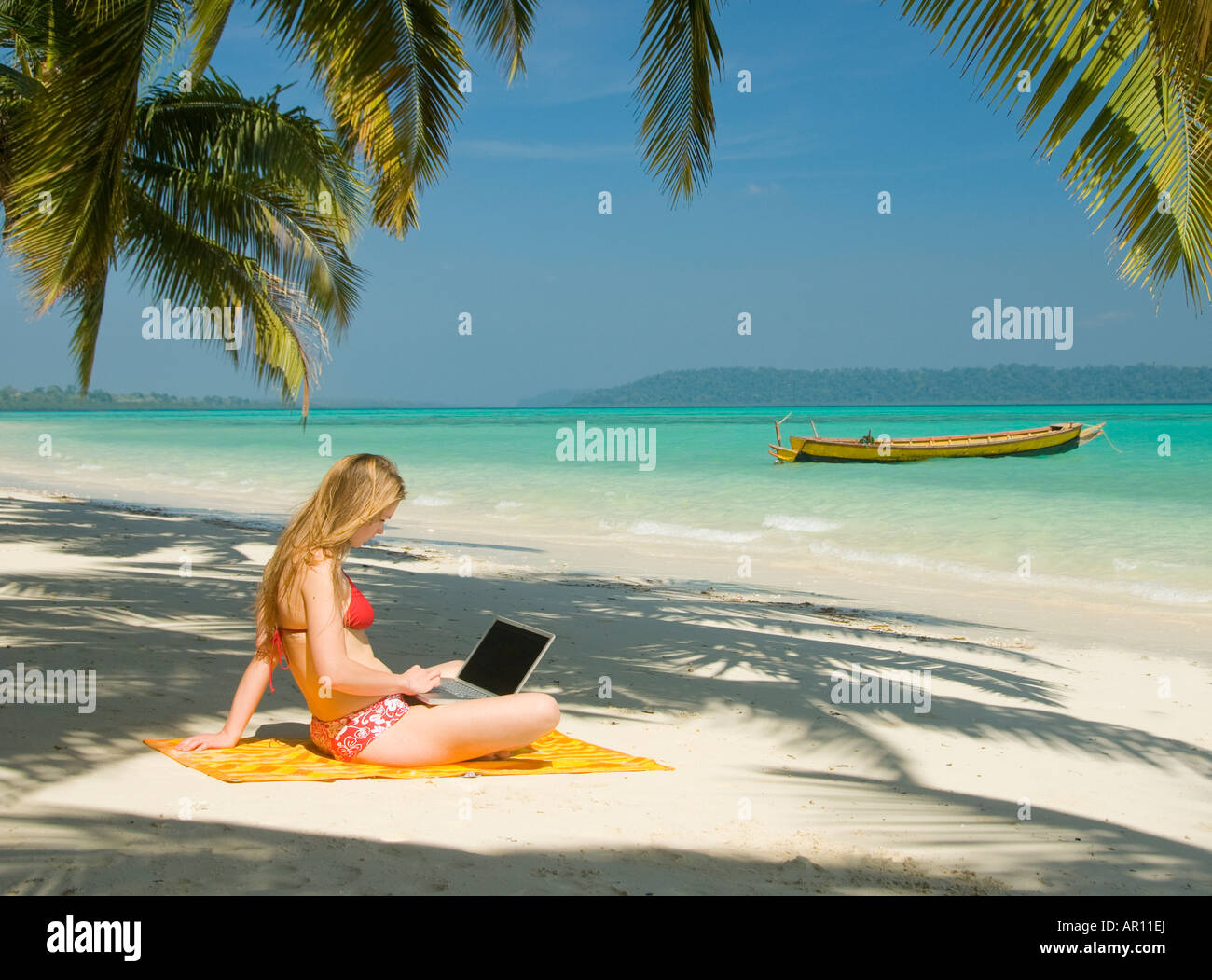 Eine Frau am Strand unter einer Palme mit einem Laptop-Computer in der Andamanen-Indien Stockfoto