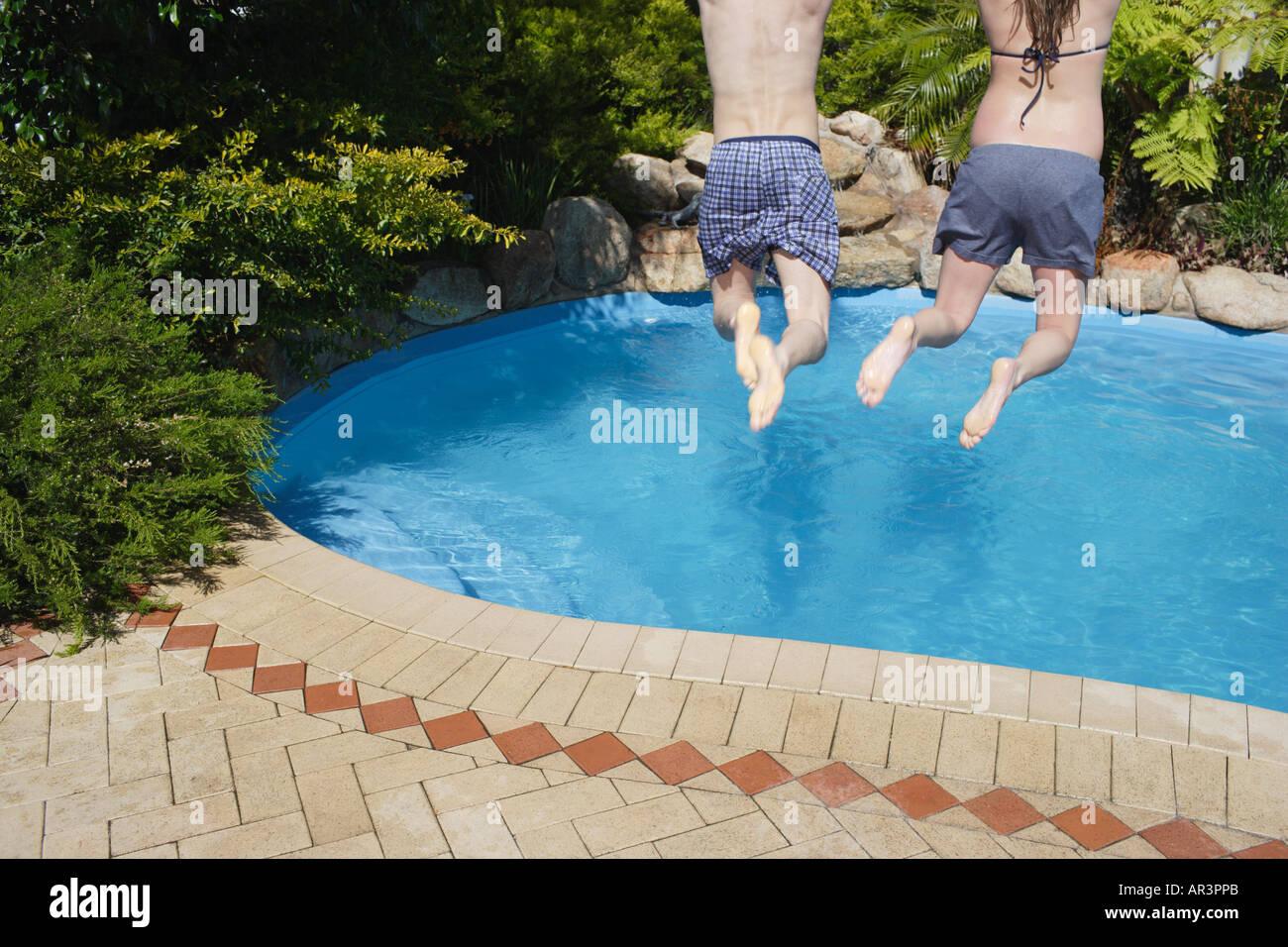 Junges Paar Sprung ins Freibad Stockbild