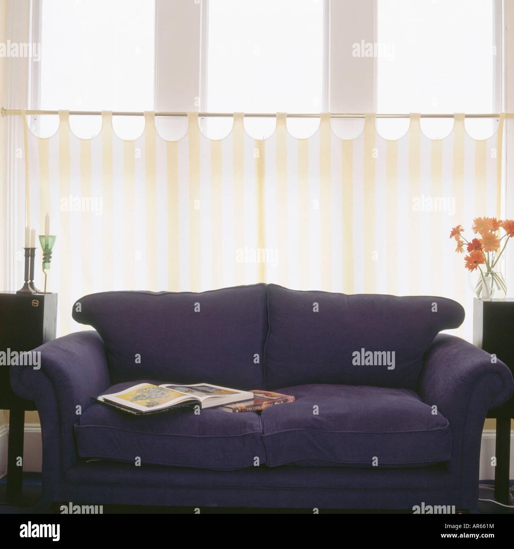 Dunkel blaue Sofa vor gelb-weiß gestreiften Café Vorhänge im ...