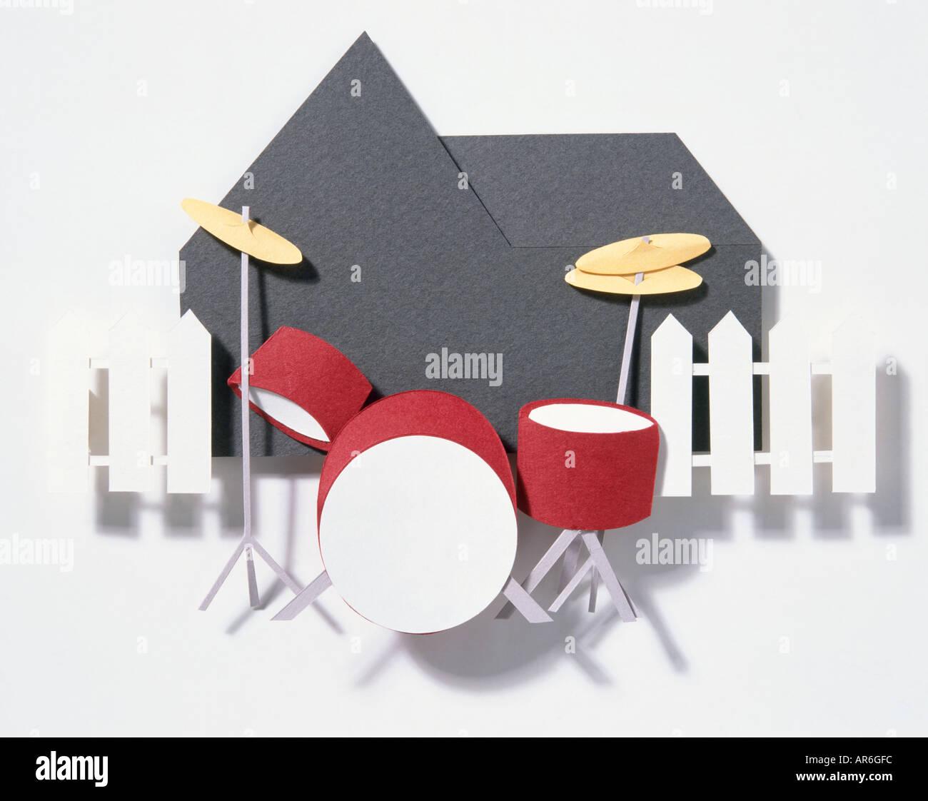 Das Papiermodell eines Drum-Kits, rot-Trommeln mit gold Symbol außerhalb schwarze Silhouette des Hauses und weißen Lattenzaun. Stockbild