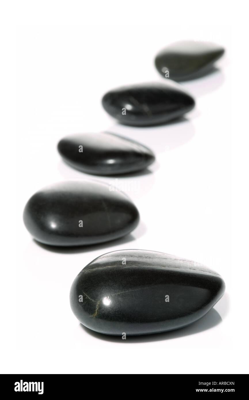 Fünf schwarze Kieselsteine in einer sanften Kurve auf einer weißen Fläche mit Reflexion High-Key Stockbild