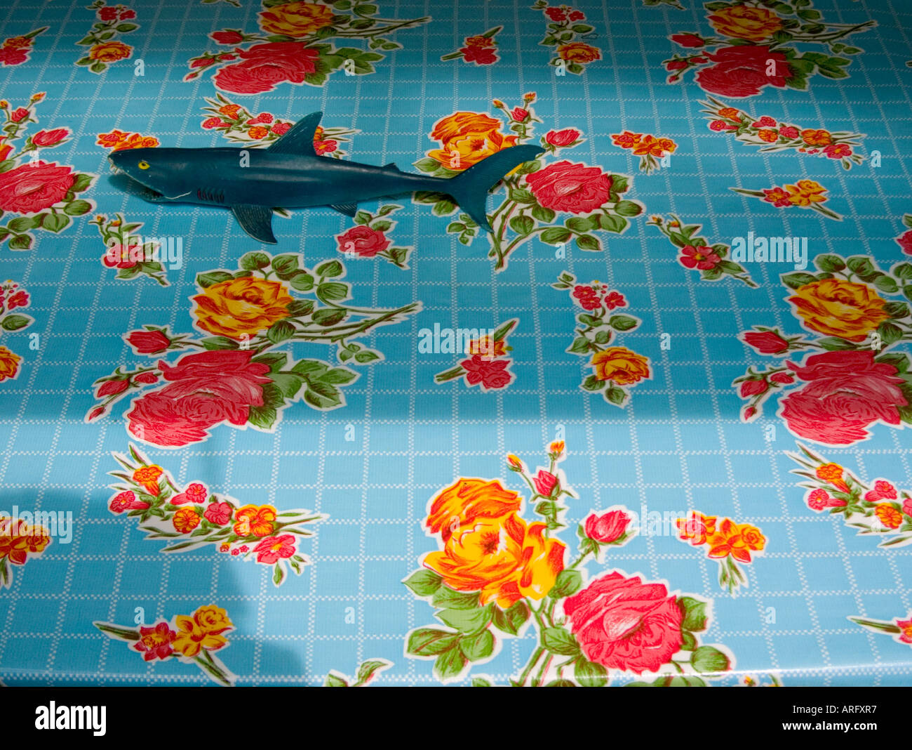 Eine Luftaufnahme von einem Spielzeug-Modell-Hai auf grellen Tischdecke mit lebendigen Rosenmuster Stockbild