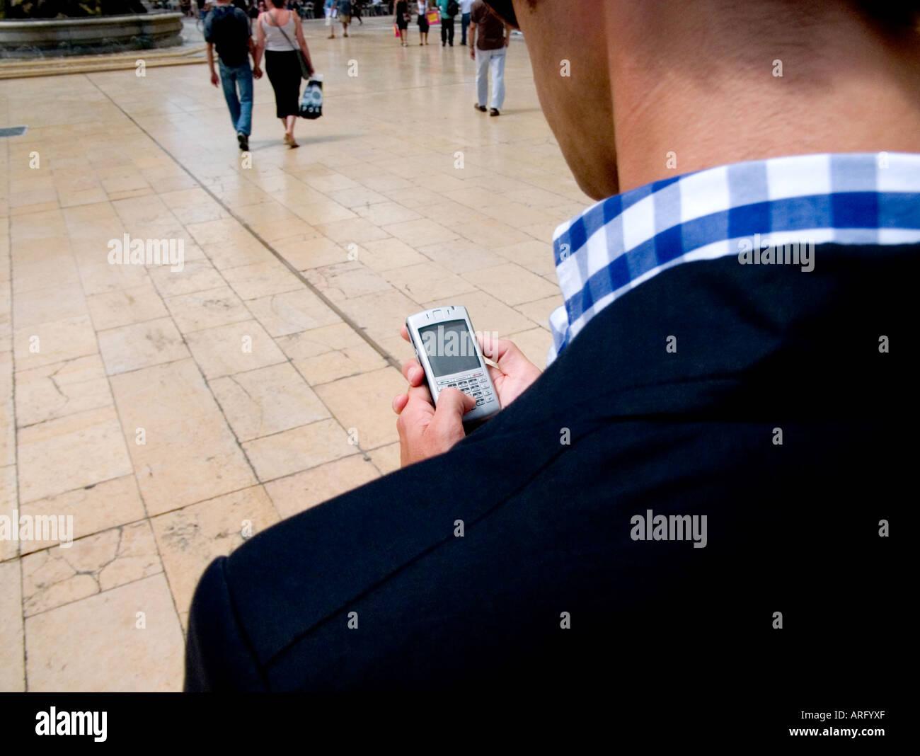 Blick über die Schulter eines kaukasischen Geschäftsmann mit Blackberry seine e-Mails lesen Stockbild