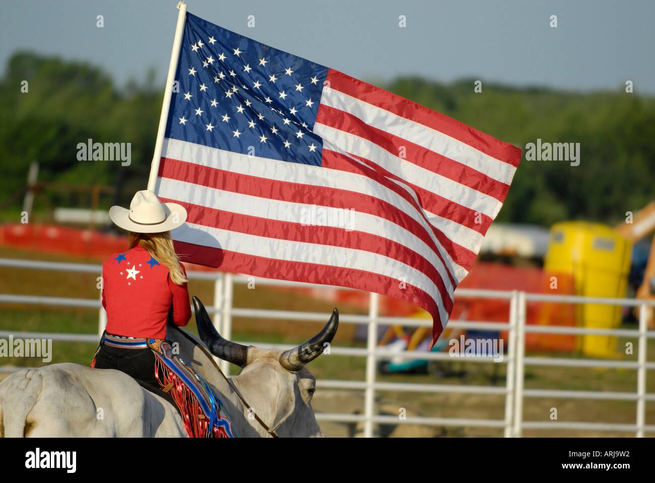 Weibliche Cowgirl reitet einen Brama Stier die Flagge in der Zeremonie vor einem rodeo Stockfoto