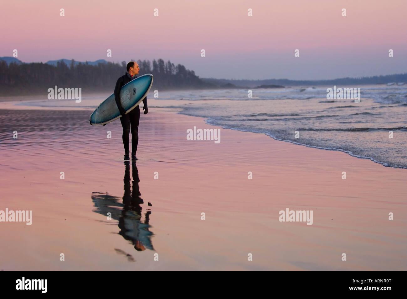 Surfer geht Küstenlinie, Pacific Rim National Park, Long Beach, Vancouver Island, British Columbia, Kanada. Stockfoto