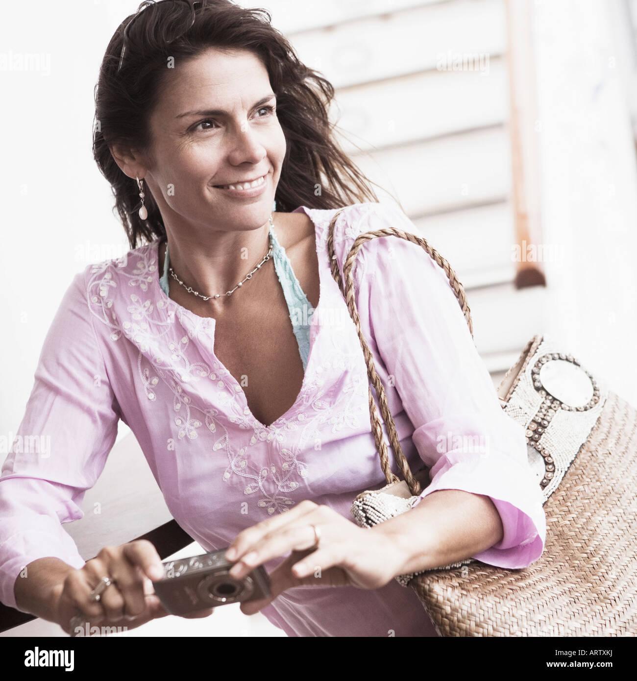 Nahaufnahme einer Mitte erwachsenen Frau hält eine digitale Kamera und lächelnd Stockfoto