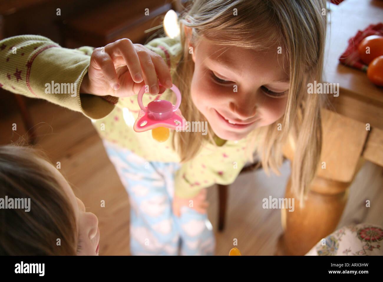 Große Schwester, kleine Schwester Schnuller geben. Stockbild