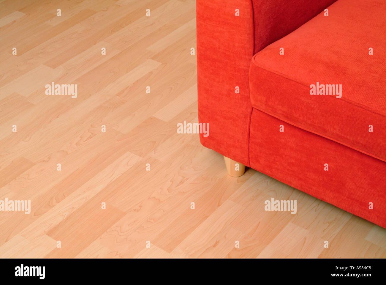 Holzfußboden ~ Rotes sofa auf einem holzfußboden stockfoto bild alamy