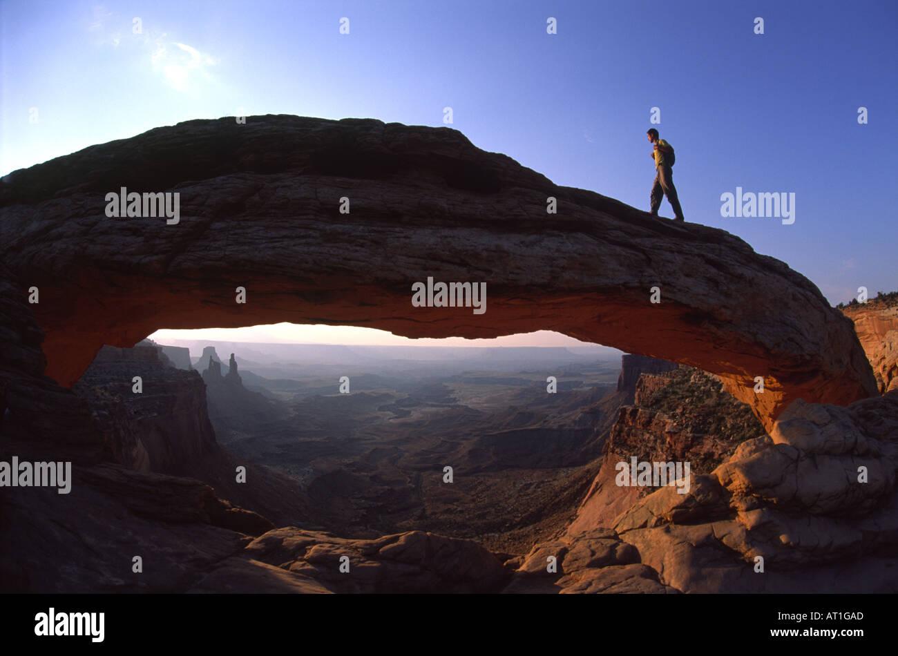 Ein Wanderer geht durch Mesa Arch bei Sonnenaufgang Canyonlands National Park in Utah USA Stockbild