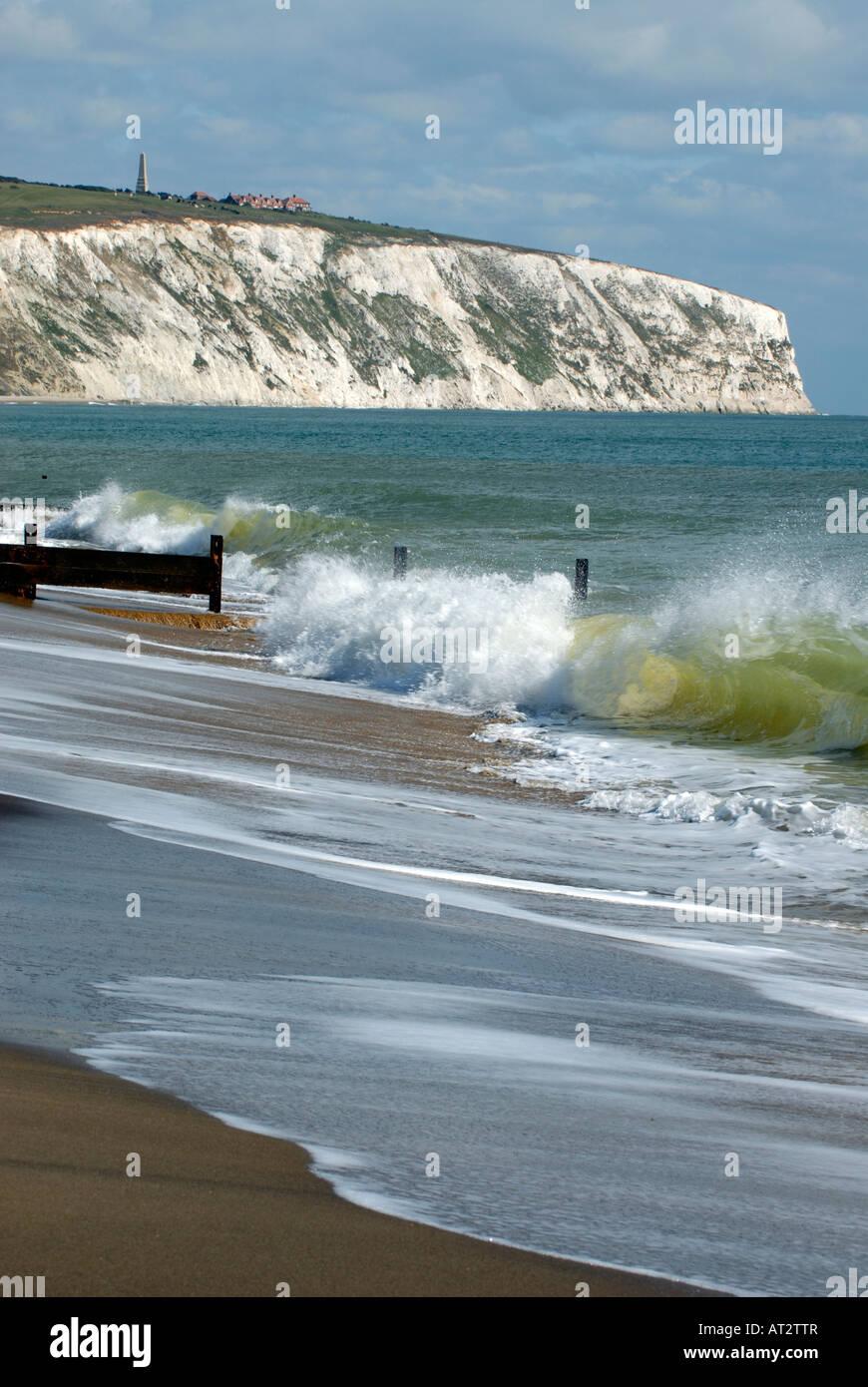 die Sandstrand mit Wellen brechen über die Buhnen und Meer Abwehrkräfte mit Klippen im Hintergrund in Stockbild
