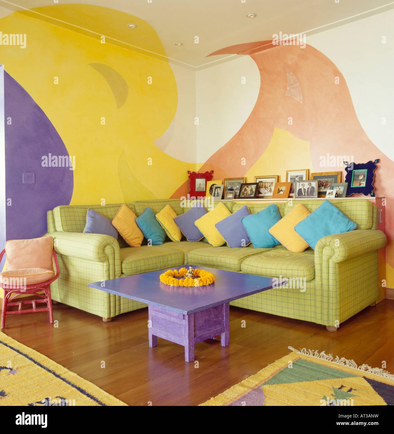 Lila Tisch und grün L-förmigen Sofa mit bunten Kissen im Wohnzimmer ...