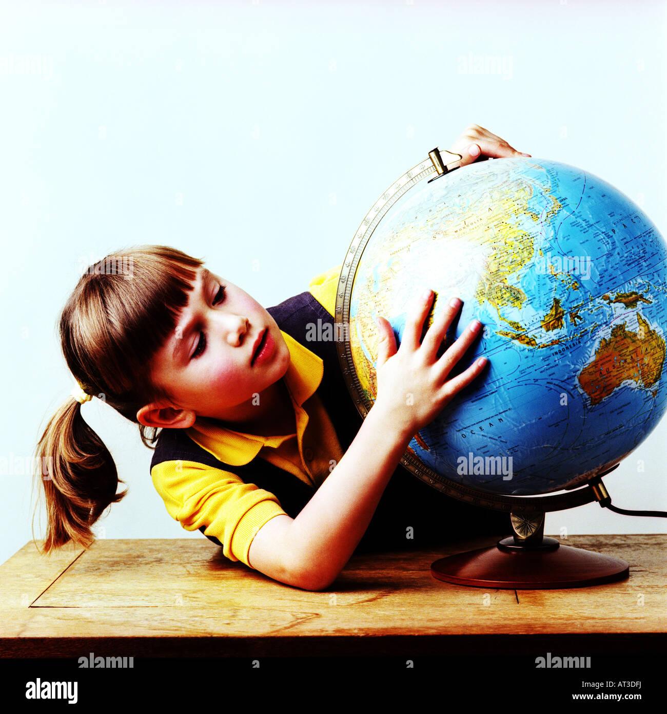 Ein kleines Mädchen auf einem Globus Stockbild