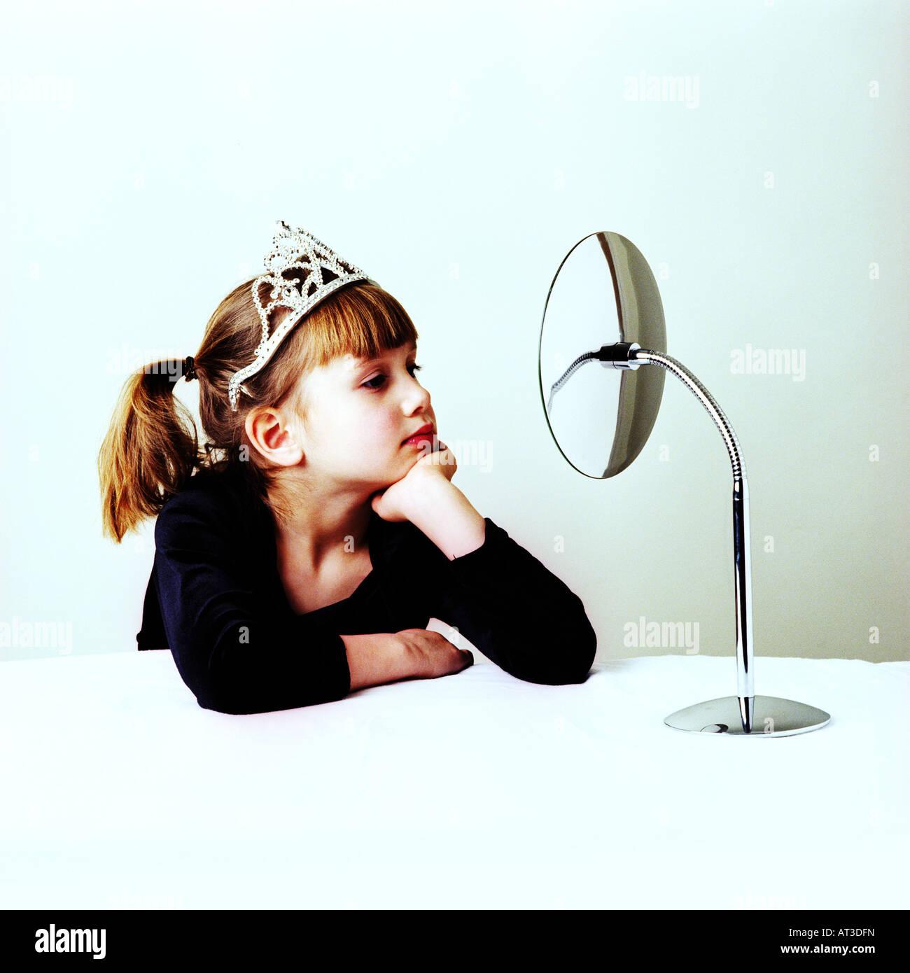 Ein Mädchen trägt eine Tiara, die sich in einem Spiegel zu betrachten Stockbild