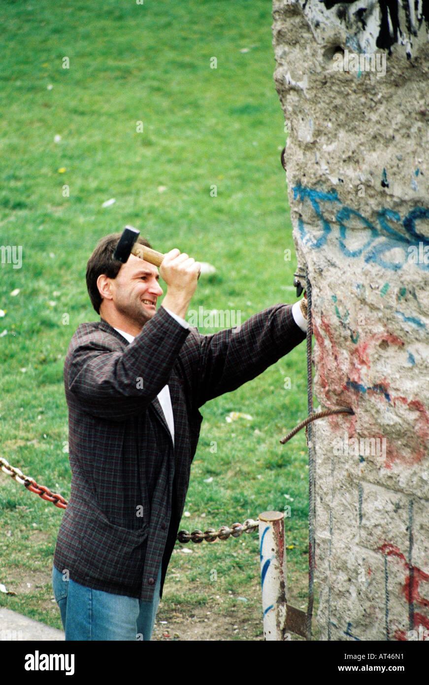 Der Fall der Berliner Mauer 1989. Ein Souvenir-Jäger schneidet Teile der Mauer. Stockbild