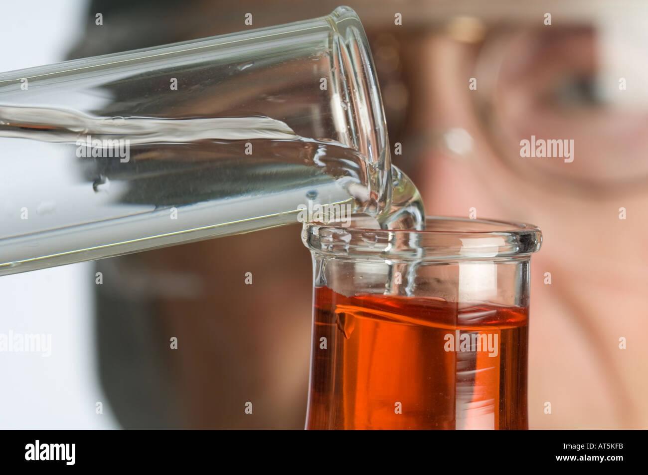 Detailansicht der Krankenschwester strömenden Flüssigkeit aus dem Reagenzglas in Erlenmeyerkolben Stockbild