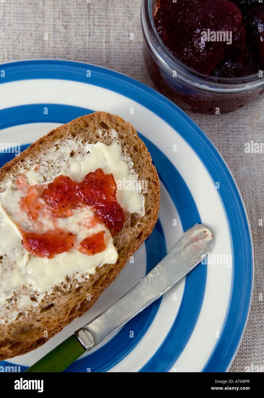 Vollkornbrot mit Bio-Butter und Erdbeermarmelade bestreichen Stockbild
