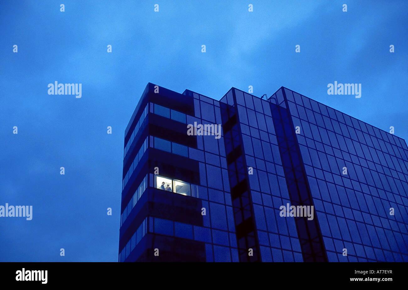 Die Fassade eines Gebäudes in der Nacht mit einem einzigen Eckbüro Licht auf Stockfoto