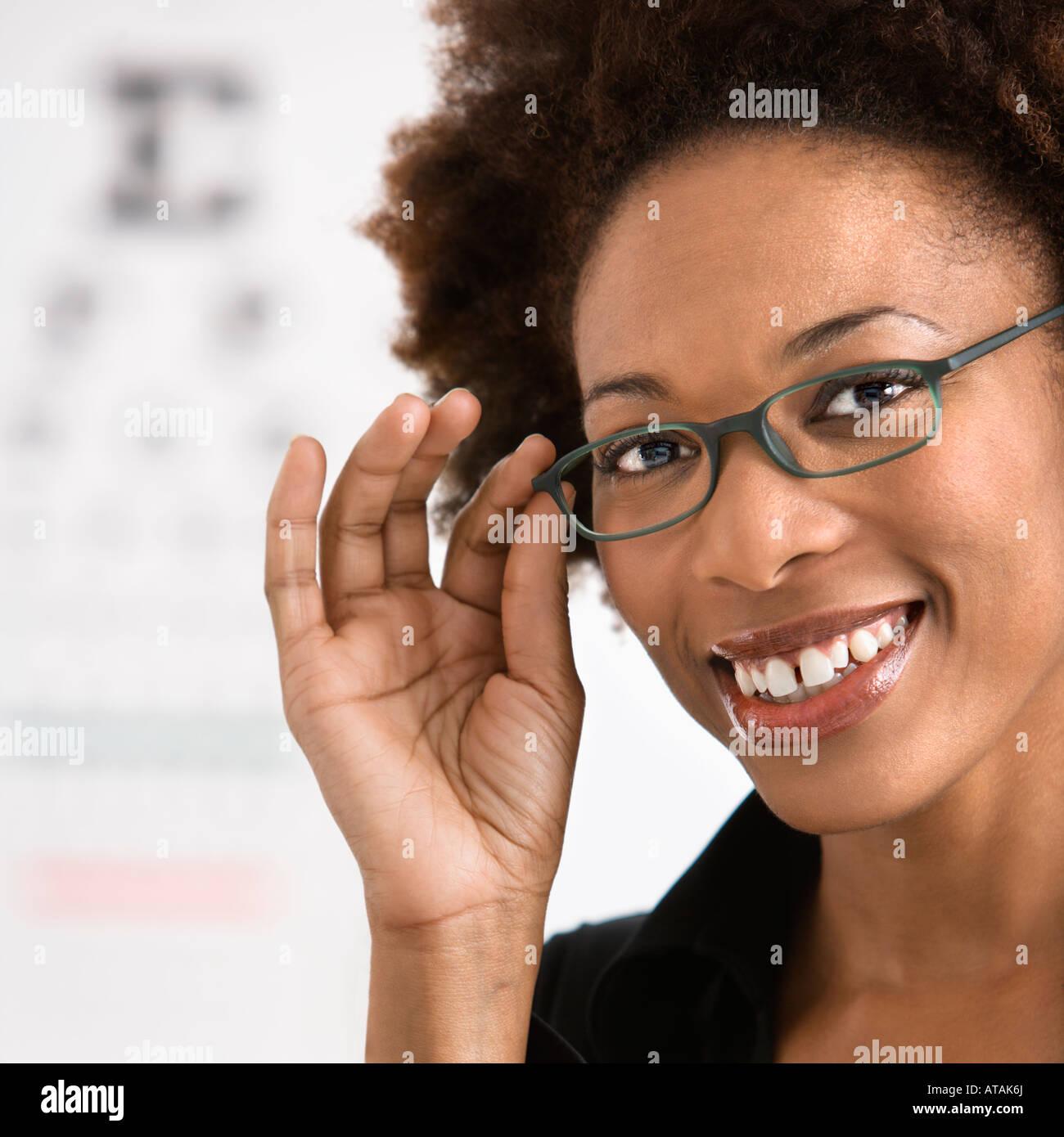 Porträt der Frau mit Afro tragen Brillen mit medizinischen Eyechart im Hintergrund Stockfoto
