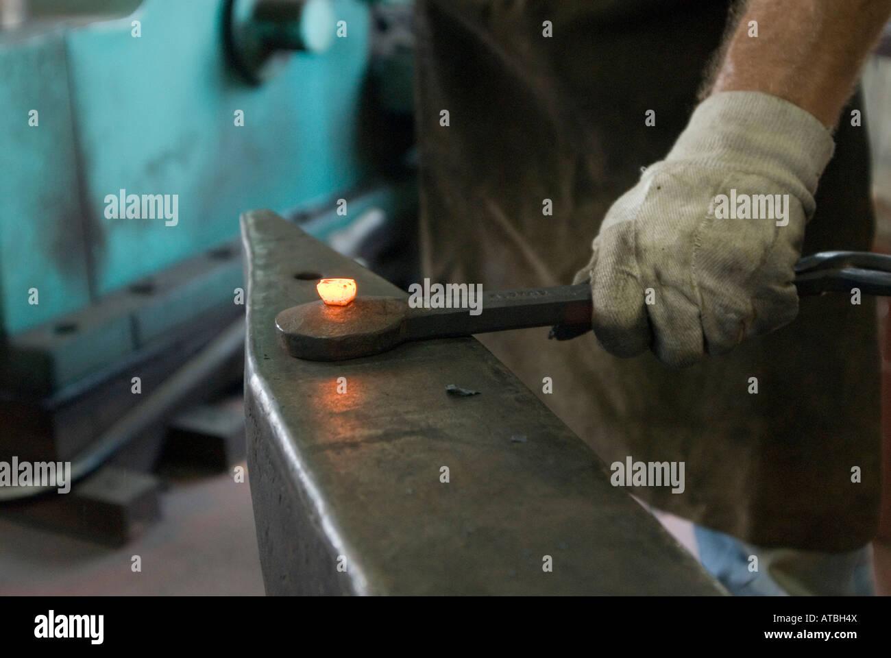 Alten Stil handgemacht Eisen Arbeiter in einen kleinen Shop Arbeitskräfte Gestaltung eine rote heiße Eisenstange Stockbild