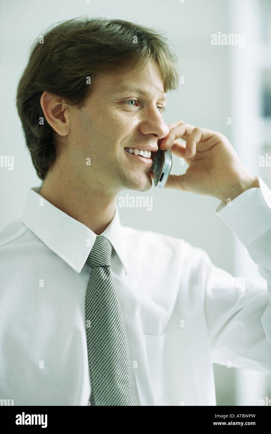 Geschäftsmann mit Handy, Lächeln, wegschauen Stockbild