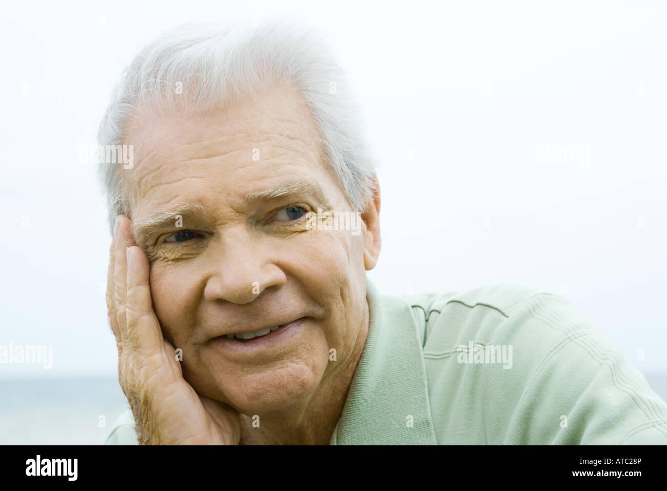 Ältere Mann mit Hand auf Wange, Lächeln, wegschauen Stockbild