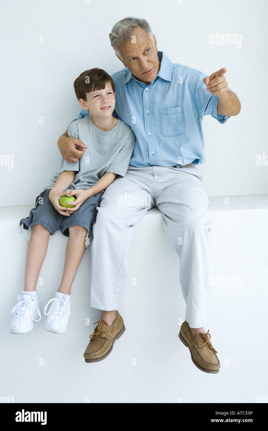 Mann, sitzend mit Arm um Enkels Schultern zeigend, beide wegschauen Stockbild