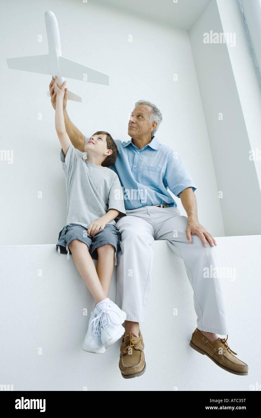 Großvater und Enkel sitzen nebeneinander, zusammenhalten, Spielzeugflugzeug Stockbild
