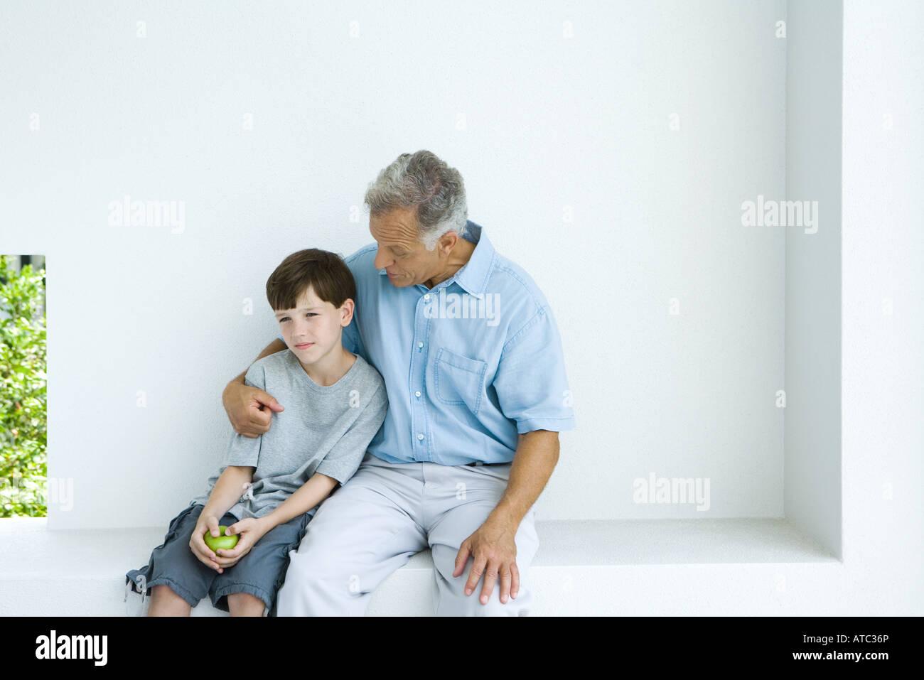 Mann, sitzend mit Arm um Enkel, chatten, beide wegschauen Stockbild