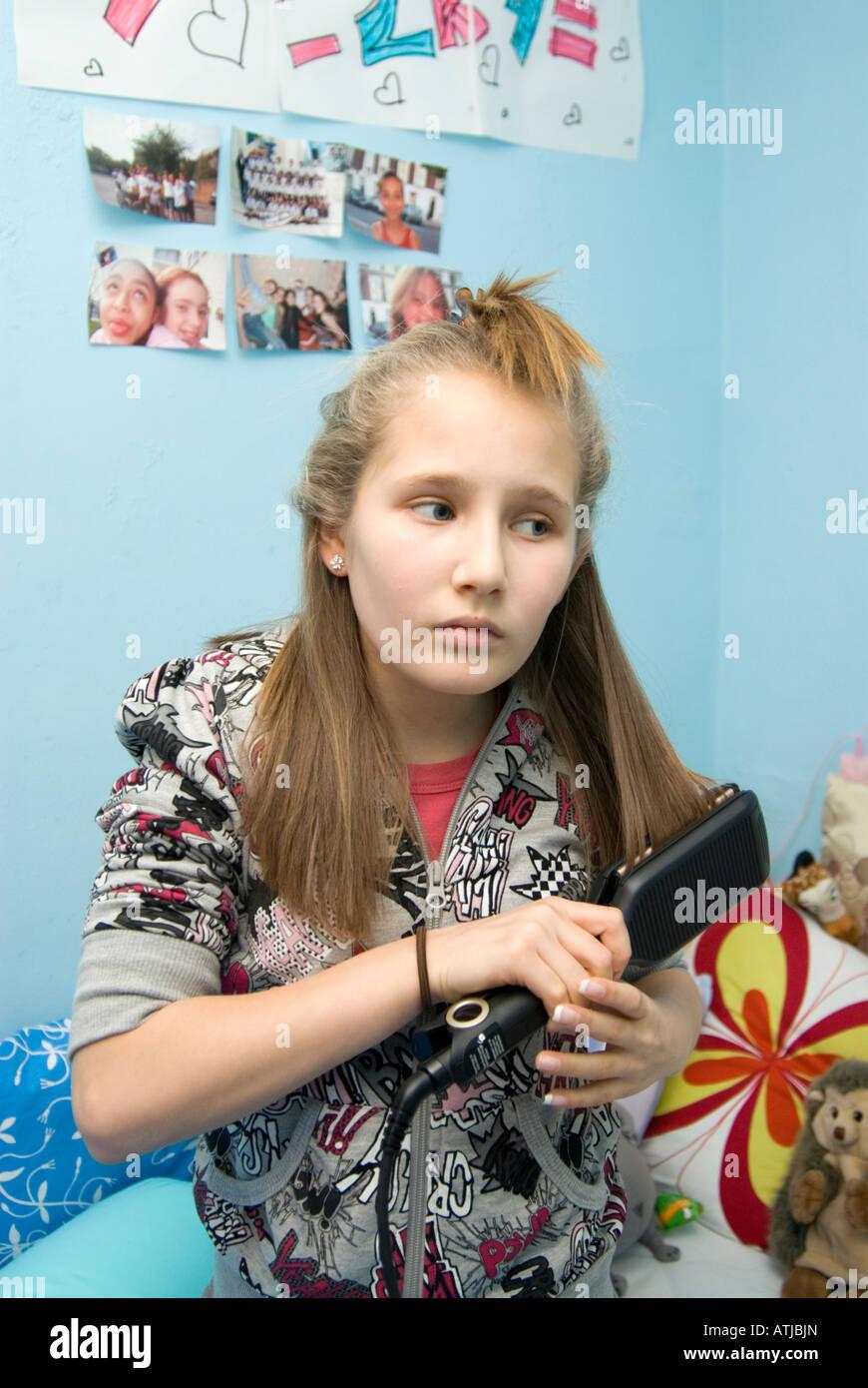 Mädchen mit Glätteisen England UK Stockbild
