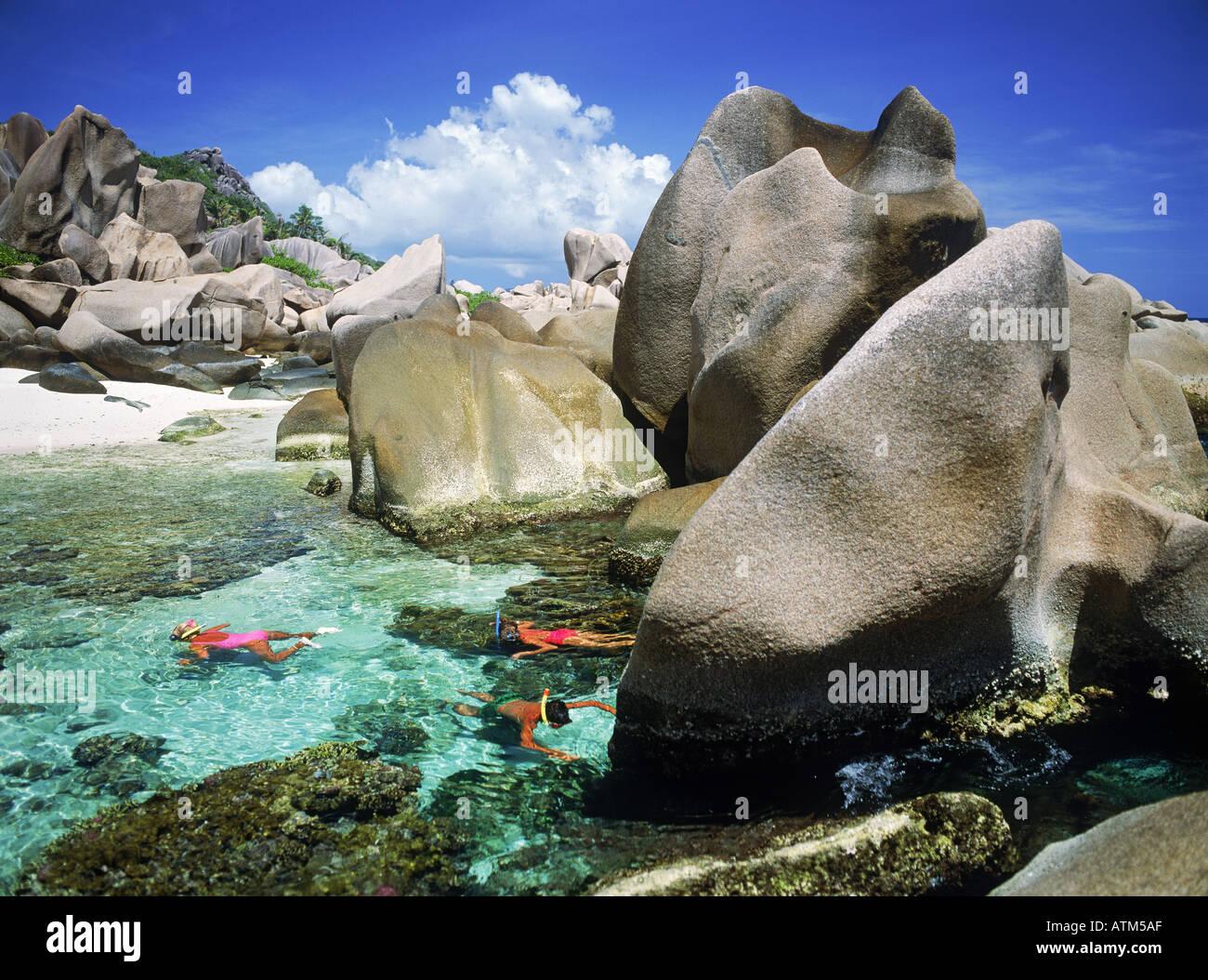 Touristen, die Schnorcheln im Gezeiten-Pools auf der Insel La Digue auf den Seychellen Stockfoto