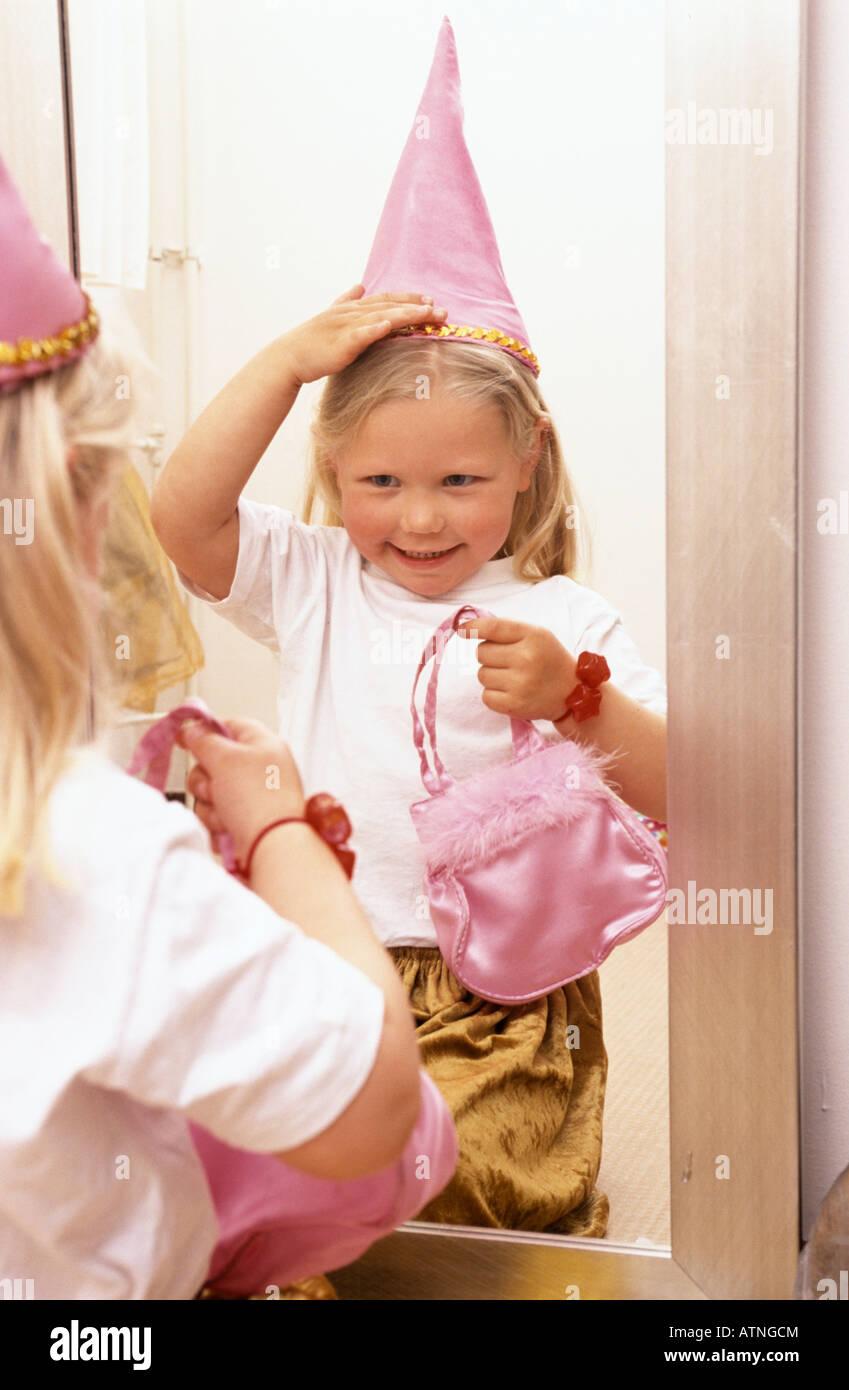 Kleines Mädchen putzt wie eine Prinzessin vor dem Spiegel Stockbild