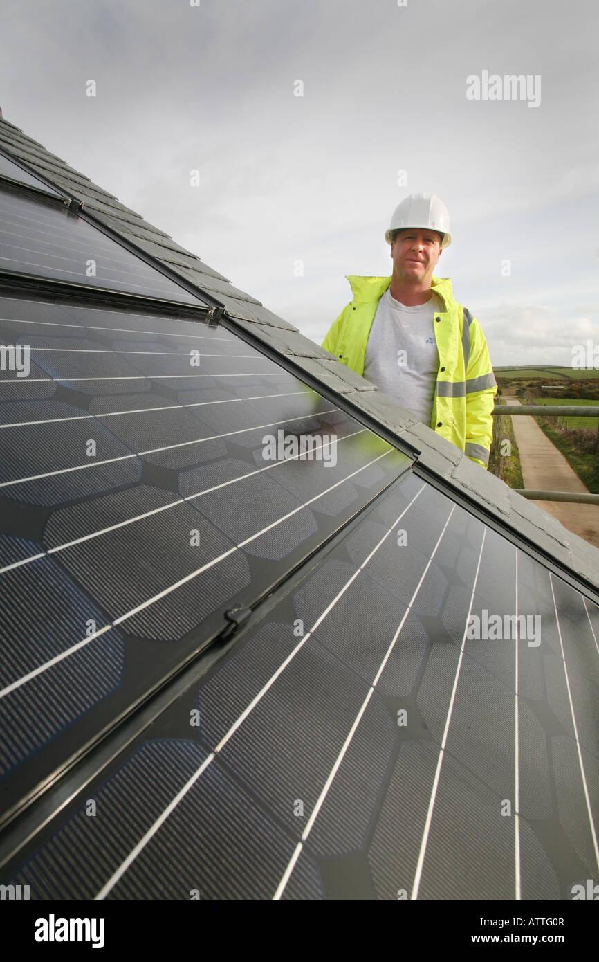 Mann mit einem Herde Hut und Hi-Vis Jacke Inspektion eines Photovoltaik-Bereichs Stockfoto