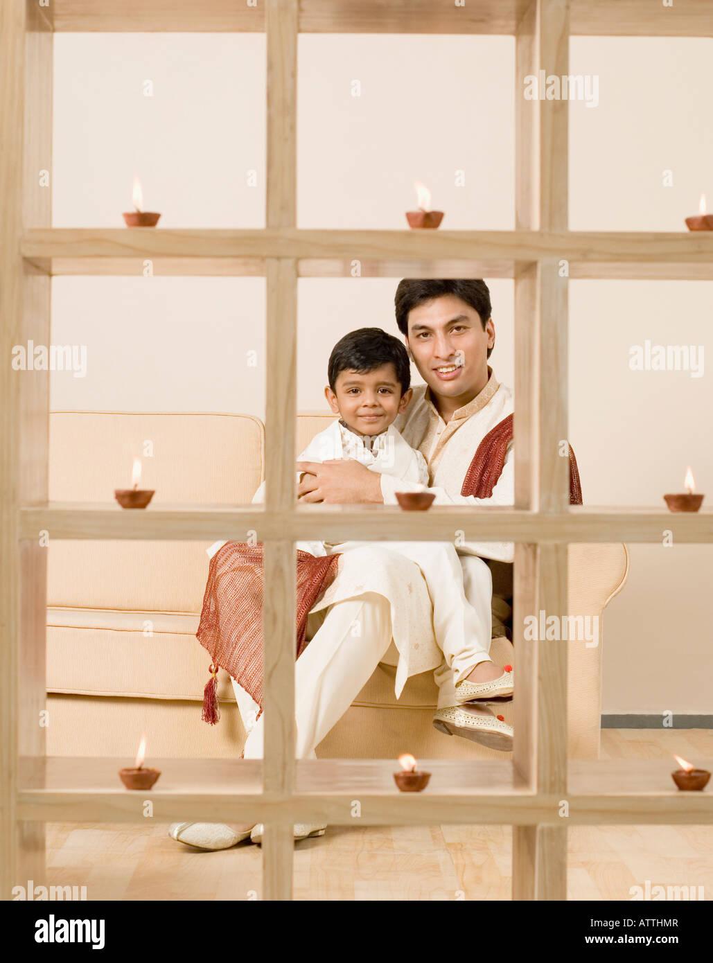 Junger Mann mit seinem Sohn auf einer Couch sitzend Stockfoto