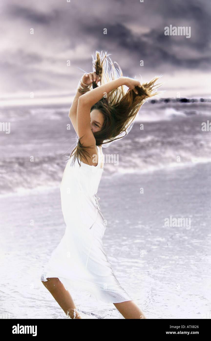 Junge Frau läuft in Ozean-Seitenansicht Stockbild