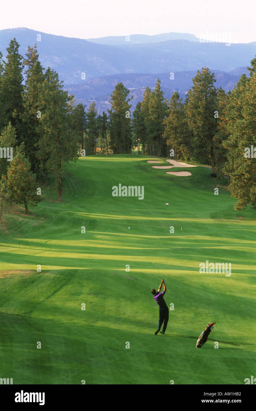 Männlichen Golfer schlagen lange Fairway erschossen im niedrigen Licht im Gallaghers Canyon Golf Club in Kelowna, British Columbia, Kanada Stockbild